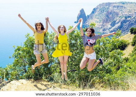 three young cheering friends jumping on a cliff above the sea