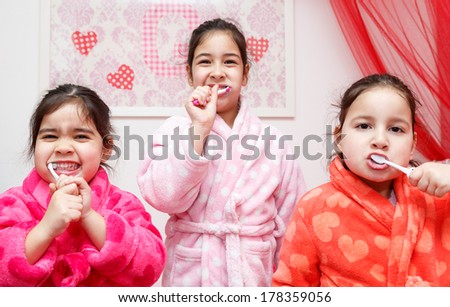 Three young children dressed in colourful dressing gowns brushing their teeth before going to bed standing in a row facing the camera in a health and hygiene concept - stock photo