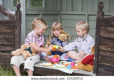 Three young children in shed playing tea and smiling - stock photo