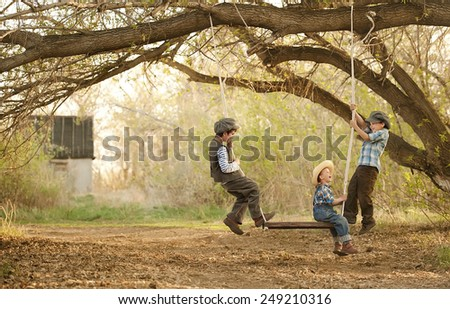 Three young children on a swing sunny summer day - stock photo