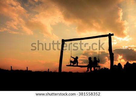 Three young children on a swing  sunset background