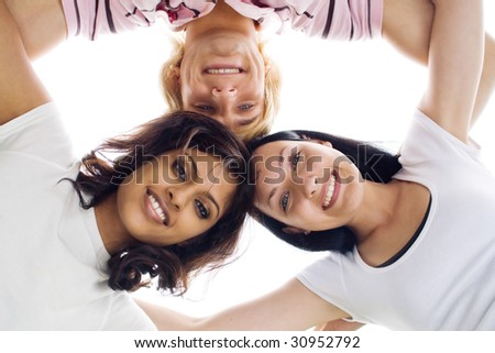 Three young college students holding there heads together. Picture taken from below.