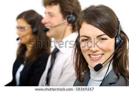 Three young customer service operators sitting in a row and talking on headset. Selective focus on women in front. Isolated on white background. - stock photo
