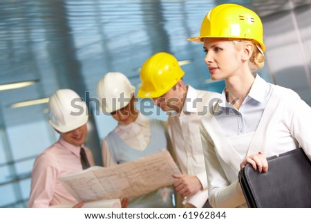 Three young engineers examining a project, one woman standing apart - stock photo