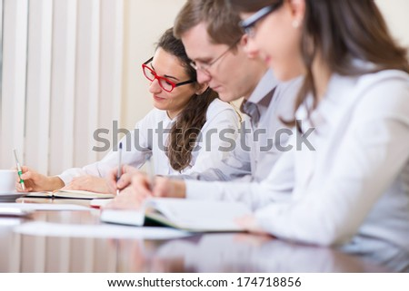 Three young executives at meeting at office - stock photo