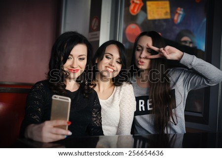 Three young female friends taking a picture of themselves on a smart phone. Hispanic, selfie