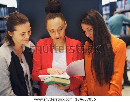 Three young female students standing in the library and looking at a book together. University students reading reference books for their studies. - stock photo