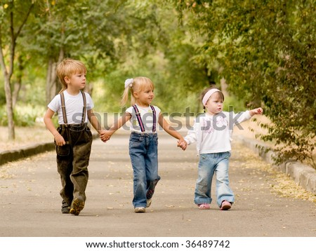 Three young friends go for a walk the park - stock photo