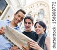 Three young friends with a map looking to camera and making tourism - stock photo
