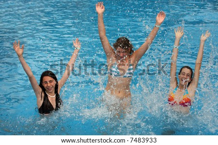 Three young girl jumps in the pool - stock photo