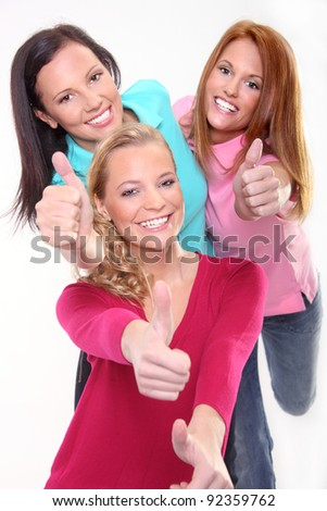 Three young girls gesturing thumb up sign - stock photo