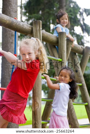 Three young girls playing in a playground. Diversity and friends - stock photo