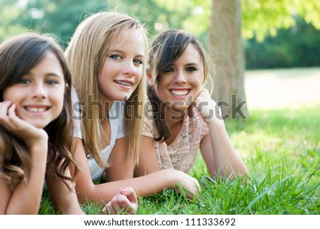 Three young girls/sisters sitting in the grass smiling - stock photo