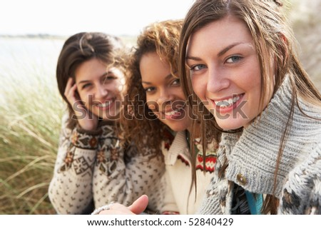 Three Young Girls Sitting In Sand Dunes Together