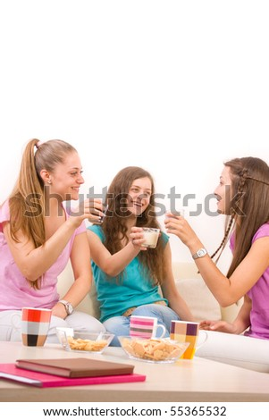 Three young girls sitting in the living room and having a drink