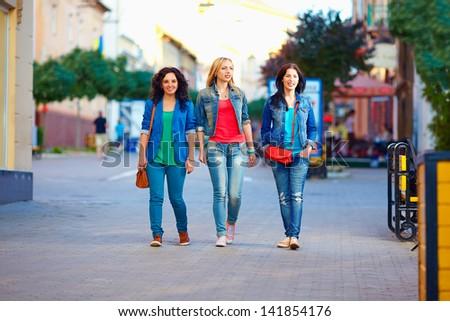 three young girls walking the city street - stock photo
