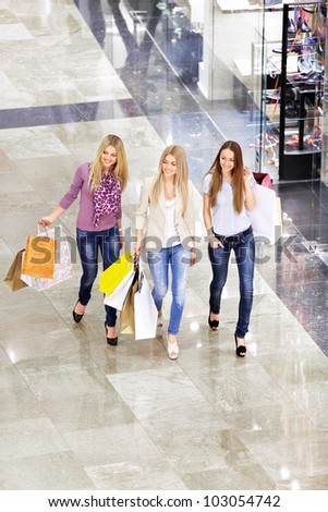 Three young girls with shopping bags in shop - stock photo