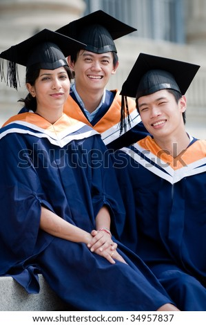 Three young graduates sitting on steps outdoors in graduate attire