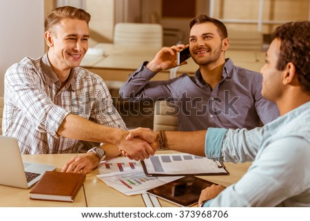 Three young handsome businessmen in casual clothes smiling, using laptop and tablet, talking on the phone while working in office. Two men shaking their hands - stock photo