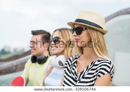 Three young happy people sitting on staircase and enjoying summer day
