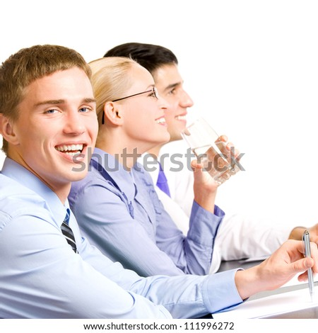 Three young happy smiling businesspeople at meeting, presentation or conference, isolated over white background - stock photo