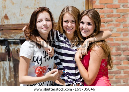 Three young happy smiling girl friends have fun & & looking at camera in city outdoors - stock photo