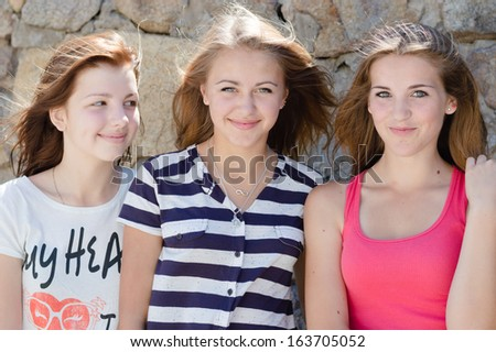 Three young happy smiling & looking at camera teenage girl friends have fun in city outdoors - stock photo