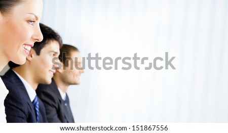 Three young happy smiling successful businesspeople at meeting, presentation or conference, with copyspace - stock photo