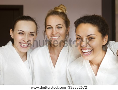 Three young happy women at spa resort. Frenship and wellbeing concept - stock photo