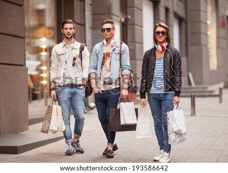Three Young male fashion metraseksualy shop shopping walk - stock photo
