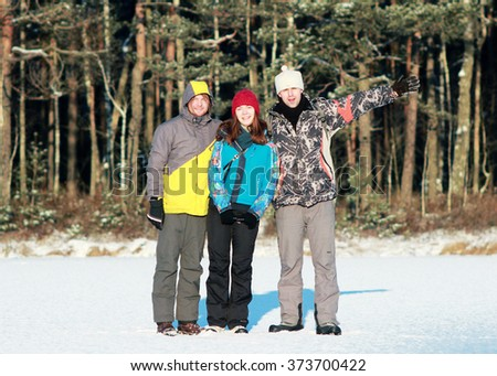 three young men and women group of people, friends and couples enjoy winter activities in winter forest scatter and throw the snow, enjoy life - stock photo
