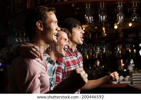 Three young men at bar watching match and shouting - stock photo