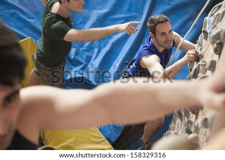 Three young men climbing in indoor climbing gym - stock photo