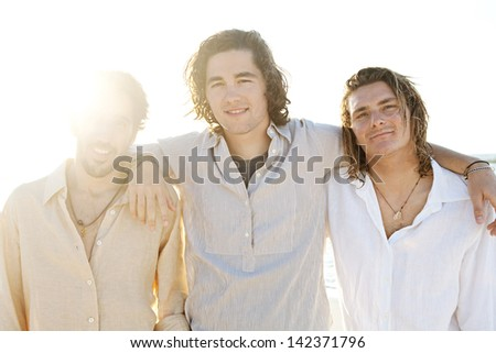 Three young men friends hanging around on vacation together with their arms around each other at sunset while on a beach having fun and smiling during the summer. - stock photo