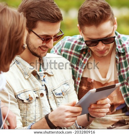 Three young men friends using tablet computer in park - stock photo