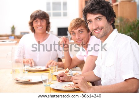 Three young men having lunch - stock photo
