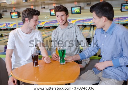 Three young men havng a drink at the bowling alley - stock photo