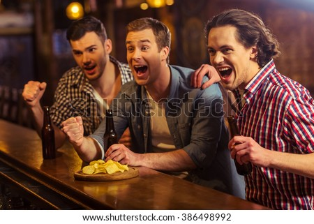 Three young men in casual clothes are cheering for football and holding bottles of beer while sitting at bar counter in pub - stock photo