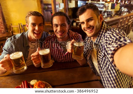 Three young men in casual clothes are smiling, taking selfie and drinking beer while sitting in pub - stock photo