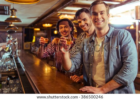 Three young men in casual clothes are talking, laughing and holding glasses of alcoholic beverage while sitting at bar counter in pub - stock photo