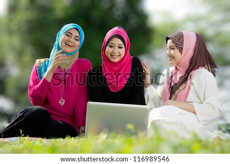 Three young Muslim women are playing a laptop while relaxing in the park - stock photo