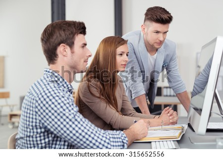 Three Young Office People Sitting at the Table and Looking at Computer Screen Together Seriously.