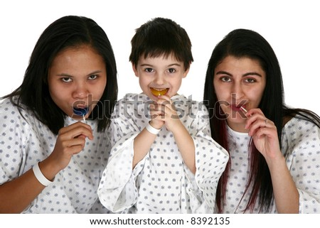 Three young patients in hospital gowns with lolipops. - stock photo