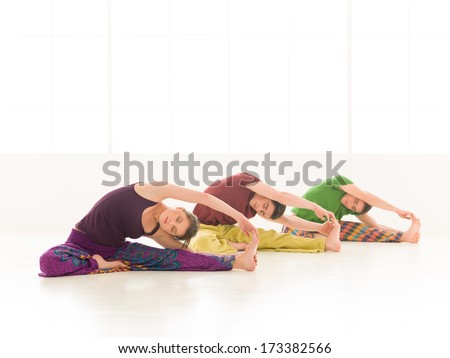 Three young people a woman and two men practice yoga class parivrtta janu sirsasana exercices, - stock photo