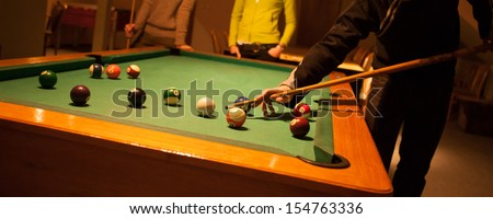 Three young people are playing billiards on table - stock photo