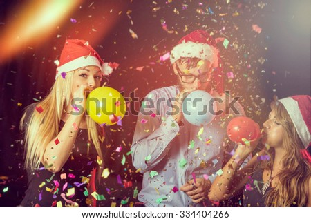 Three young people at New Year's Eve party on midnight blowing colorful balloons and having fun - stock photo
