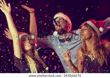 Three young people blowing party whistles at a New Year's Eve party - stock photo
