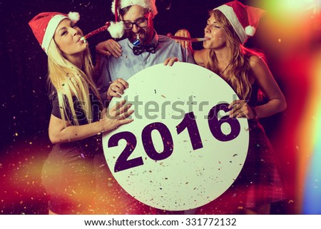 Three young people, having fun at New Year's Eve Party, blowing whistles and holding cardboard blank circle. - stock photo