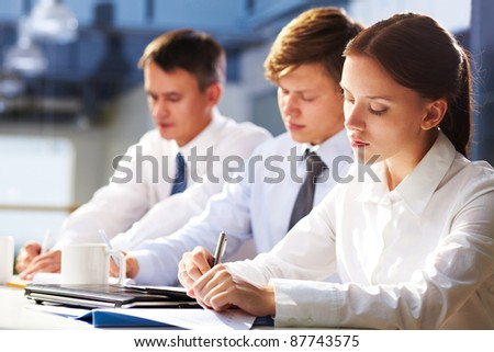 Three young people making notes at lecture - stock photo