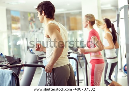 Three young people running on treadmill in fitness club